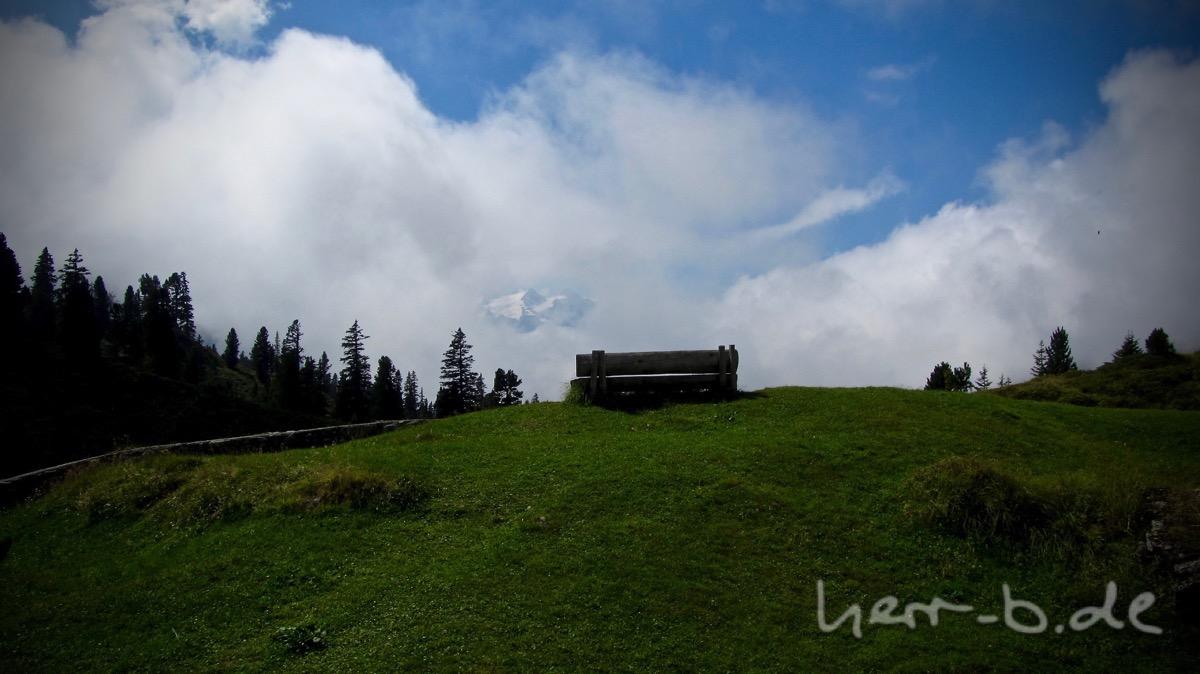 Aussichtsbank mit Guckloch im Wolkenvorhang.