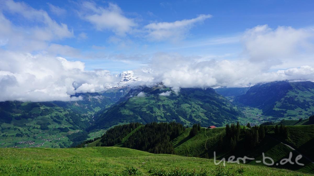 Weiße Berggipfel schauen zwischen den Wolken hindurch.