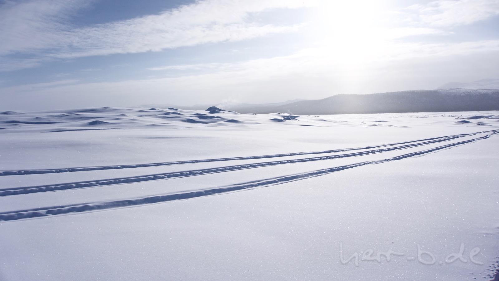 Dampfende Löcher im Eis auf dem Stausee Tjaktjajaure.
